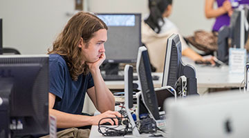 Student working at a computer in a computer lab.